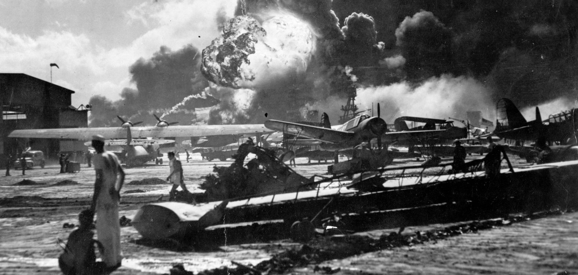 Sailors stand amid wreckage watching as the USS Shaw explodes on Dec. 7, 1941, at the Naval Air Station, Ford Island, Pearl Harbor.