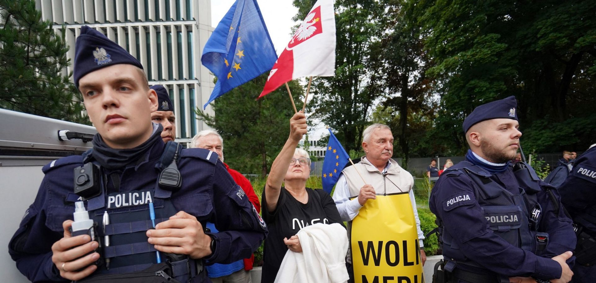 Police stand guard in Warsaw, Poland, as demonstrators holding EU and Polish flags protest the country's proposed media law on Aug. 10, 2021.