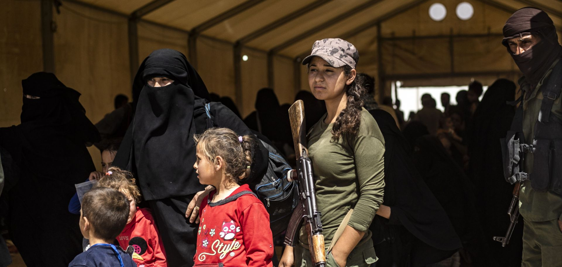 Fighters with the U.S.-backed, Kurdish-led Syrian Democratic Forces guard women and children waiting to leave the al-Hol camp in northeastern Syria on June 3, 2019.
