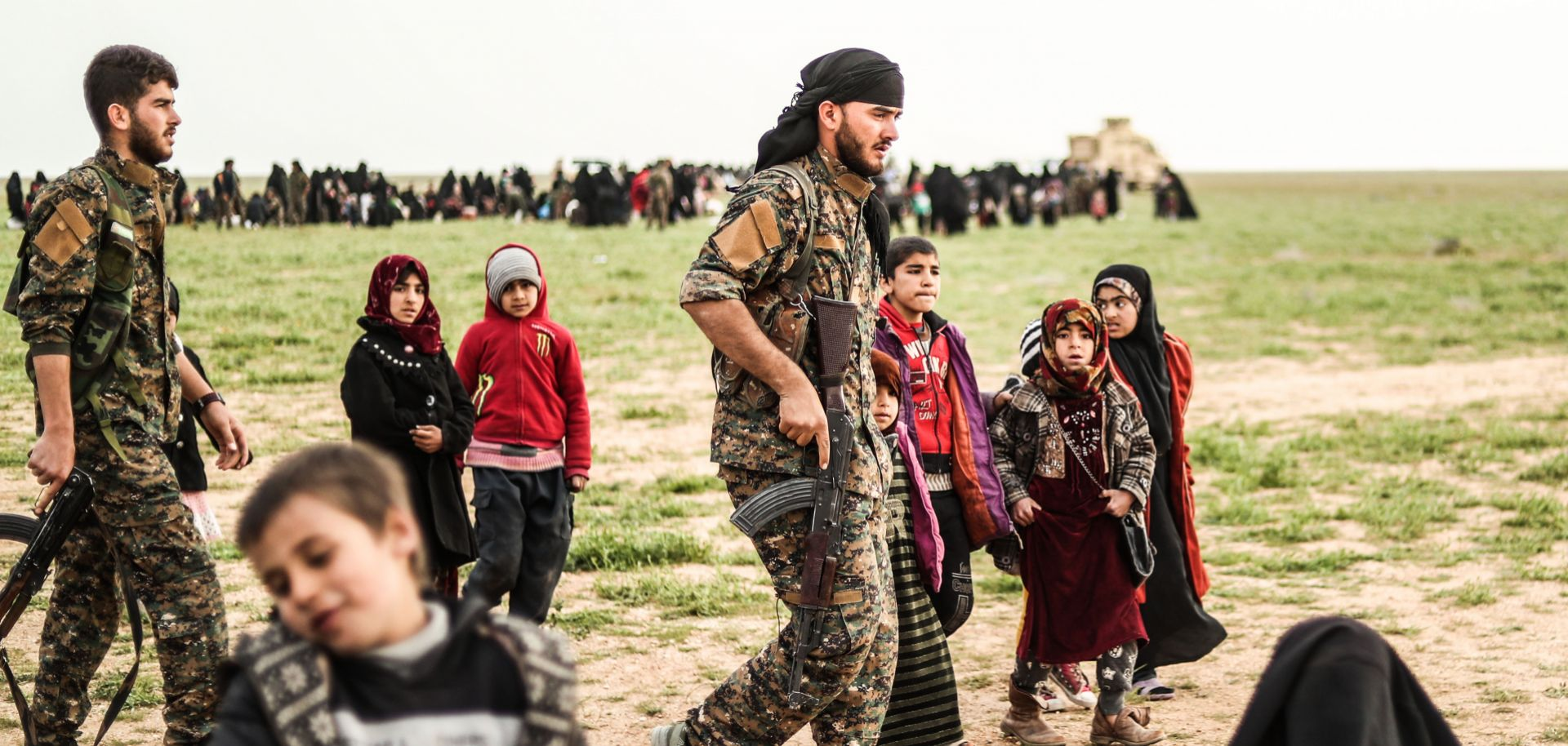 Fighters with the Syrian Democratic Forces walk past civilians at a screening area for evacuees from the Islamic State's embattled holdout in Baghouz, Syria, on Feb. 26, 2019.