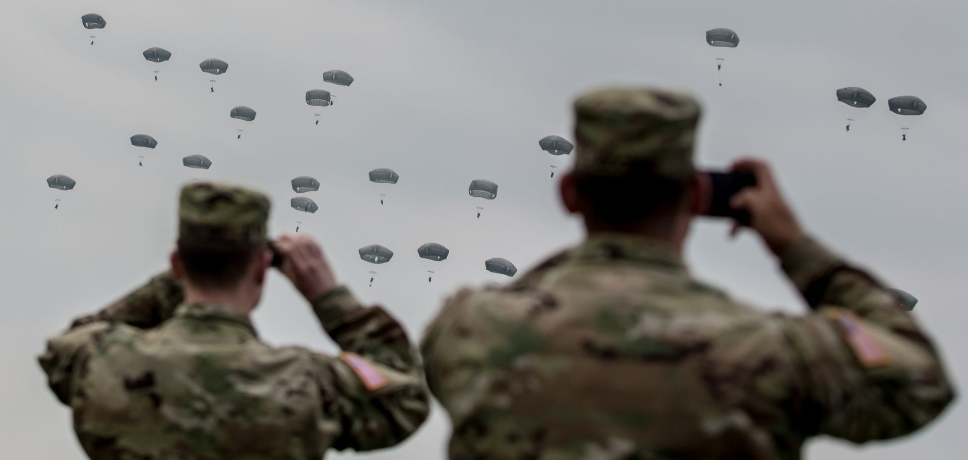 U.S. soldiers watch paratroopers from the U.S. Army 173rd Airborne Brigade, the UK's 16 Air Assault Brigade and Italian Folgore Airborne Brigade as they parachute to the ground during a training jump as part of the Saber Junction 16 military exercises near the Hohenfels Training Area. April 2016, near Grafenwoehr, Germany.