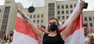 A woman wearing a face mask holds the former flag of Belarus at an anti-government protest in Minsk on Aug. 14, 2020.