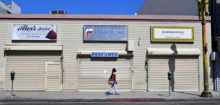 A woman walks past closed shopfronts in what would be a normally busy fashion district in Los Angeles, California, on May 4, 2020.