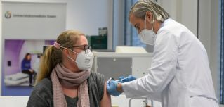 A hospital worker receives a dose of a COVID-19 vaccine in Essen, Germany, on Jan. 18, 2021.