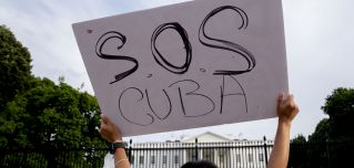 A demonstrator holds up a sign in solidarity with protesters in Cuba outside the White House on July 18, 2021.