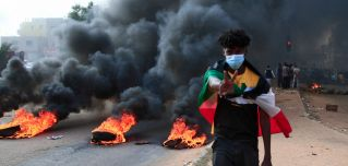 A protester draped with Sudan's national flag stands in front of burning tires during a demonstration in Khartoum on Oct. 25, 2021.