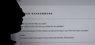 An IT researcher stands next to a giant screen of a computer infected by ransomware at High Security Laboratory of the National Institute for Research in Computer Science and Automation in Rennes, France, on Nov. 3, 2016.
