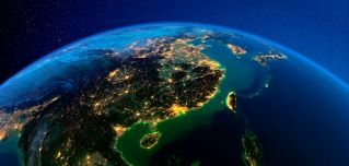 A 3D rendering of eastern China and the island of Taiwan lit by city lights from space.