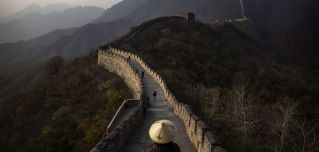 Tourists walk down part of the Great Wall of China.