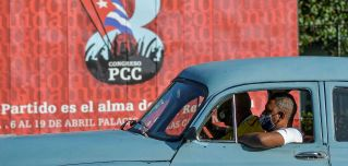 A motorist passes a sign for the 8th Congress of the Cuban Communist Party on April 6, 2021, in Havana.