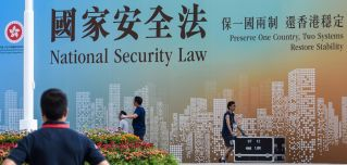 Technicians in Hong Kong walk next to a banner supporting China's new national security law following a flag-raising ceremony marking the 23rd anniversary of the city's British handover on July 1, 2020.