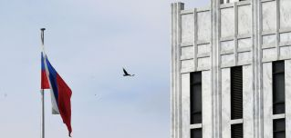 A bird flies past the flag outside the Russian embassy in Washington D.C. on April 15, 2021.