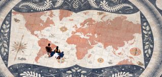 People stand over a world map at the Monument to the Discoveries in the Belem parish of Lisbon, Portugal, on Aug. 21, 2014.