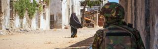A soldier of the Kenyan Contingent serving with the African Union Mission in Somalia (AMISOM) keeps watch on a street in the center of the southern Somali port city of Kismayo on October 5, 2012. Meanwhile, a combat engineering team inspects the surrounding area following reports of a suspected improvised explosive device (IED) left behind by the Al-Qaeda-affiliated extremist group Al Shabaab.