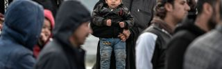 Refugees and migrants stand at a port upon arriving at the Greek island of Lesbos on March 7, 2020.