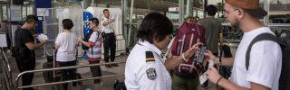 Security staff check passengers boarding passes at the entrance of Hong Kong International Airport.
