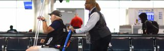 A customer care agent employed by G2 Secure helps a disabled passenger get to his boarding gate at Denver International Airport in Denver, Colorado.