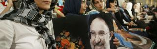 A woman holds a picture of outgoing reformist President Mohammad Khatami on July 31, 2005, during a ceremony in Tehran marking his last week of service.