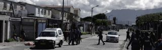 Residents gather as South African police officers respond to a shooting of two alleged gang members in Cape Town in 2017.