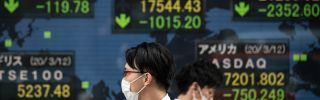 Pedestrians wearing face masks walk past an electric board showing the Nikkei 225 index (C) on the Tokyo Stock Exchange in Tokyo on March 13, 2020.