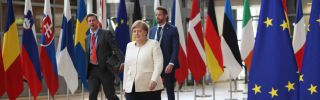 Angela Merkel walks down a red carpet lined with flags as she arrives at the Europa Building in Brussels, Belgium.