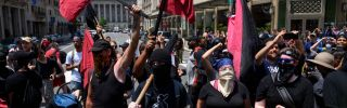 """Members of an antifa group march as the Alt-Right movement gathers for a """"Demand Free Speech"""" rally in July 6, 2019, Washington."""