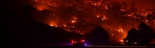 A fire truck drives past a hill engulfed in flames on the night of Jan. 20, 2020 in Mount Adrah, Australia. The 2020 fire season has hit the southern coast of New South Wales particularly hard.