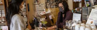 A shopkeeper wearing a protective mask serves a client on April 22, 2020, in Berlin from behind a protective plastic screen in a coffee store open for the first time since a COVID-19 shutdown.