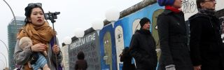 Visitors walk by East Side Gallery section of the former Berlin Wall during celebrations for the 25th anniversary of the fall of the wall that partitioned Germany during the Cold War, Nov. 9, 2014.