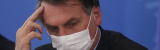 Wearing a protective mask, Brazilian President Jair Bolsonaro takes to questions regarding the country's coronavirus outbreak during a press conference at the Planalto Palace in Brasilia on March 18, 2020.