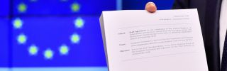"""European Council President Donald Tusk holds the """"draft agreement of the withdrawal of the United Kingdom of Great Britain and Northern Ireland from the European Union"""" during a press conference at the European Council in Brussels on Nov. 15."""