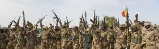 Members of the Chadian Army raise their weapons.