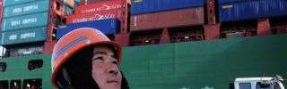 A worker watches cranes at the port in Qingdao, China, on Feb. 15.