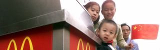 Chinese children peek from behind a trash can at a McDonald's in Beijing in October 2000, the month the United States granted China permanent normal trade relations.