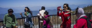 Chinese tourists take photographs at Mount Fuji in Japan.