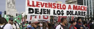 """Marching demonstrators hold a banner reading """"Take Macri away, leave us the dollars"""" during a partial strike against the economic policies of the government of Argentina's President Mauricio Macri on April 30, 2019."""