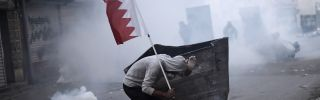 A Bahraini protester takes cover during clashes with police on the outskirts of Manama in 2015.