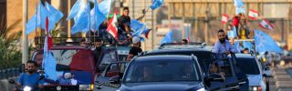 Supporters of Lebanon's Future Movement party wave the party's flag alongside the country's national flag during a parade in the southern Lebanese city of Sidon on Oct. 22, 2020.