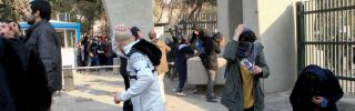 Students at the University of Tehran run for cover as tear gas is lobbed at demonstrators on Dec. 30, 2017.