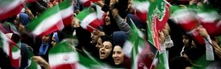 Iranian schoolgirls wave their country's flag at a rally on the anniversary of Iran's Islamic revolution.