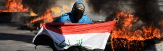 An Iraqi demonstrator poses with the national flag as angry protesters blocked roads in the central city of Najaf on Jan. 5, 2020, to oppose the possibility that Iraq would become a battleground between the United States and Iran.