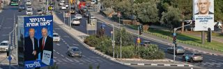 Election billboards for the Likud party and the Blue and White party line a street in Israel.