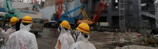 Tokyo Electric Power Co. workers outside the Unit 4 reactor building at the Fukushima Dai-ichi nuclear plant on June 12.