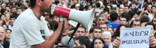"""Armenian demonstrators raise a placard reading """"Put an end to embezzlement"""" during a protest against an increase of electricity prices in Yerevan on June 24. (KAREN MINASYAN/AFP/Getty Images)"""