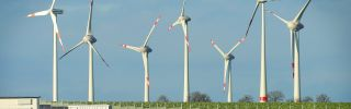 Wind turbines stand behind a solar power park on Oct. 30, 2013, near Werder, Germany.