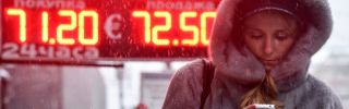 A woman in Moscow walks past a sign showing the Russian ruble's value compared the the U.S. dollar and euro.