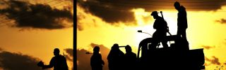 Libyan rebels are silhouetted at sunset on March 7, 2011. Three years later, an Islamist coalition would mount another revolt meant to topple the country's newly elected government.