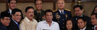 Philippine President Rodrigo Duterte, center, poses with lawmakers, leaders of the Moro Islamic Liberation Front and military and police officials during a presentation ceremony for the new Bangsamoro law in Manila on Aug. 6, 2018.