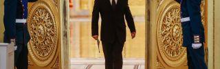 Russian President Vladimir Putin enters a hall.
