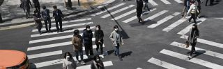 Pedestrians wearing face masks cross an intersection in Seoul, South Korea, on April 23, 2020. In the first quarter of 2020, South Korea's economy saw its worst performance in more than a decade as COVID-19 spread across the country.